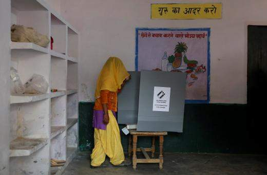 A woman looks at the Electronic Voting Machine (EVM) before casting her vote inside a booth at a polling station (Image | Reuters)