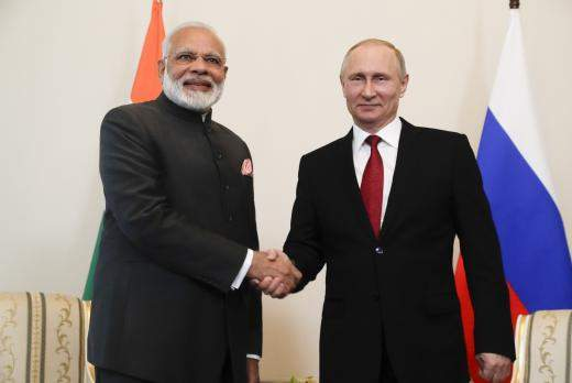 Russian President Vladimir Putin (R) shakes hands with Indian Prime Minister Narendra Modi during a meeting (Image | Reuters)