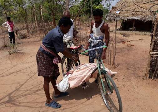 The body of the old woman being taken on a bicycle.