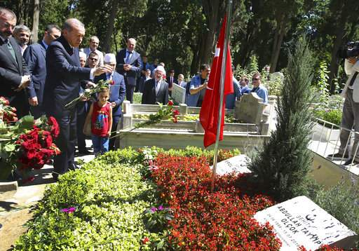 Turkey's President Recep Tayyip Erdogan, left, throws flowers onto the grave of a victim of last year's failed coup attempt, in Istanbul, Tuesday, July 11, 2017. Erdogan and Turkey's Prime Minister Binali Yildirim, visited a graveyard in Istanbul where some of the victims were buried, while special prayers were to be recited in honour of the dead at mosques across the country. (AP)
