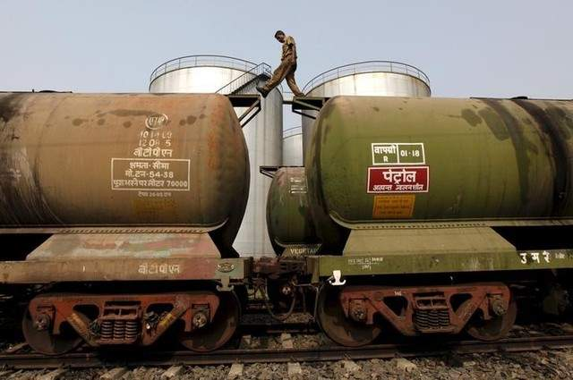 A worker walks atop a tanker wagon to check the freight level at an oil terminal on the outskirts of Kolkata, India November 27, 2013.| REUTERS