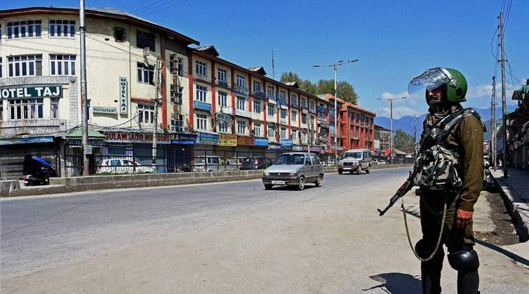 Security personnel stand guard on deserted street during a curfew in Srinagar|PTI