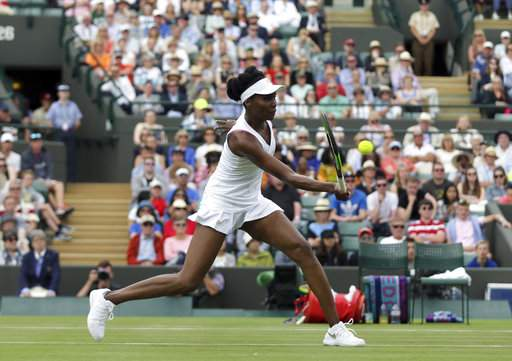 Venus Williams of the United States returns to Belgium's Elise Mertens during their Women's Singles Match on the opening day at the Wimbledon Tennis Championships in London Monday, July 3, 2017. (AP Photo)